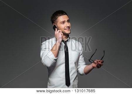 Smiling young businessman holding glasses and talking on cell phone over grey background