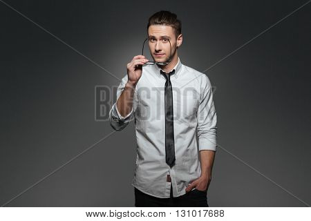 Handsome young businessman in white shirt and tie standing and holding glasses over grey background