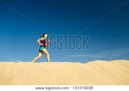 Young woman running on beautiful inspirational desert dunes or beach on sunny summer day. Beauty female runner jogging and exercising outdoors in nature Gran Canaria Canary Islands.