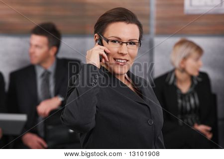 Portrait of happy businesswoman standing in office lobby, talking on mobile phone, smiling.