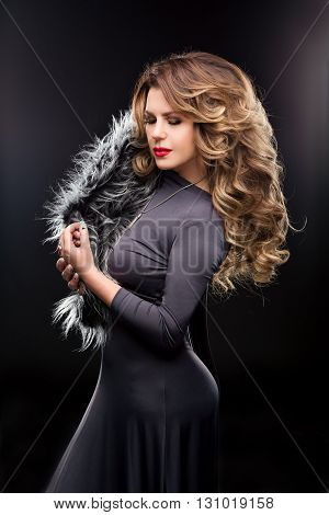 Fashion Studio portrait of beautiful woman in a gray dress with curvy figures. Slender girl with long hair. Hairstyle wavy hair streaked, makeup, red lips, fur. Black background