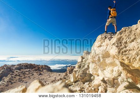 Man tourist hiker or trail runner looking at beautiful inspirational landscape in mountains. Fit runner with arms outstretched happiness freedom and enjoy inspiring view on rocks top of Tenerife.