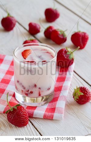 tasty healthy strawberry yogurt with strawberry pieces on a wooden table