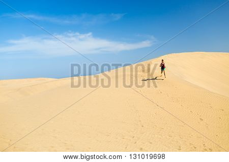 Woman running on beautiful inspirational desert dunes or beach on sunny summer day. Beauty female runner jogging and exercising outdoors in nature Gran Canaria Canary Islands.