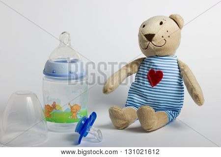 Baby bottles pacifiers and toys lying on a white background. Kids' things.