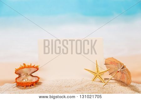 Blank white card, a casket with a pearl and starfish in the sand on the seashore.