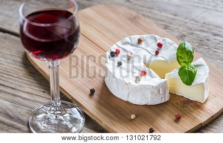 Camembert cheese on the wooden board with glass of wine