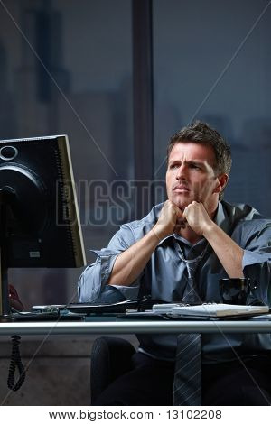 Determined businessman concentrating hard on difficult computer task working late in office looking worried.