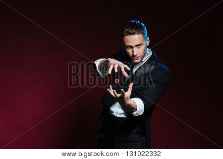 Concentrated young man magician conjuring tricks with red dice  over dark background
