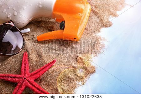 Sunscreen Spray And Sunglasses On Sand In Table