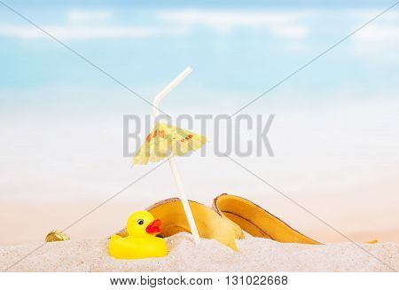 Diverse trash and rubber duck on a sea beach.