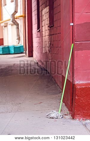 Lonely broom against gate at spring day