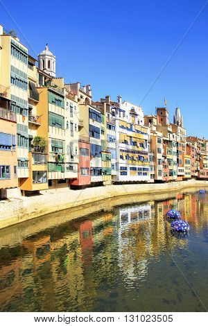 GIRONA SPAIN - MAY 10 2015: Flowers and house's reflection in Onyar River during Festival of floral decorations in Girona, Catalonia,  Spain
