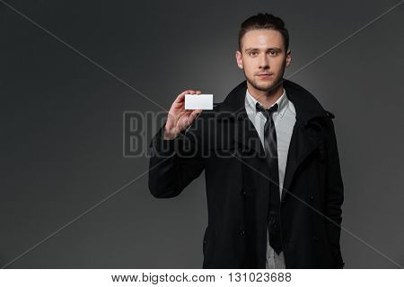Attractive young businessman in black coat standing and holding blank business card over grey background