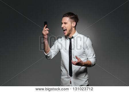 Angry crazy young businessman holding smartphone and shouting over grey background