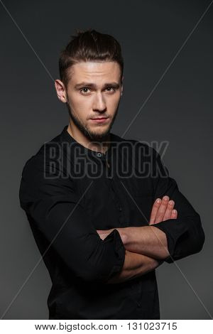 Portrait of attractive confident young man standing with arms crossed over grey background