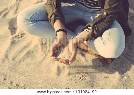 Girl In Coat And Jeans Sitting On The Beach Cross-legged, In Her Palms Sand