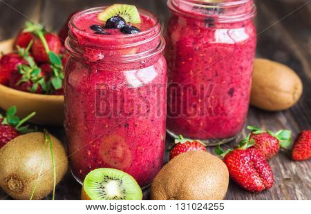 Smoothie with strawberries kiwi and blueberries in jars on rustic wooden background. Healthy breakfast.