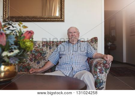 Indoor shot of happy senior man sitting relaxed on a couch at old age home. He is looking at camera and smiling.