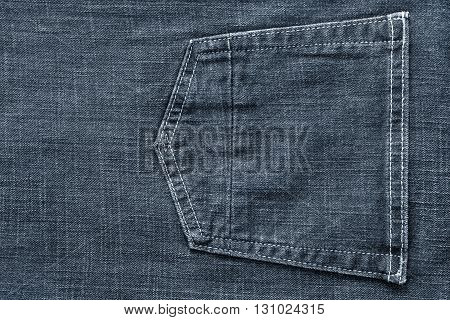fragment of trousers from jeans material or jeans clothes with the big sewn pocket closeup for the textile textured background of pale color