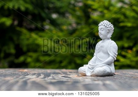 Sculpture of Buddha become enlightened on green background. Yoga and meditation concept.