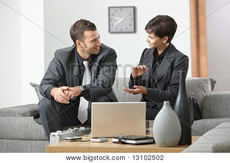 Young business people having meeting at office sitting on sofa businesswoman explaning to businessman.