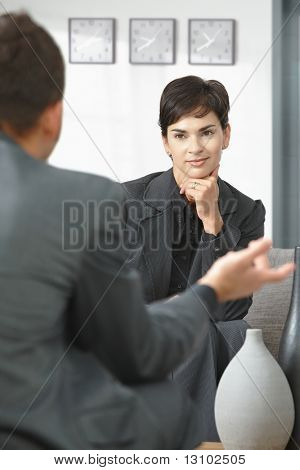 Young businesswoman sitting on sofa at office listening to talking businessman, smiling.