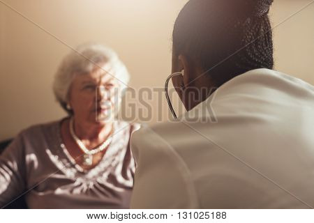 Female doctor with stethoscope examining senior woman patient