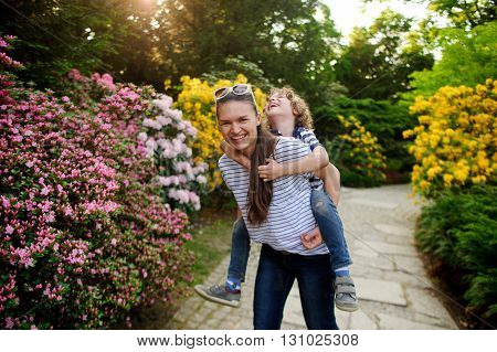 The picturesque a flowering garden. The girl plays with a 8-9 year old boy. They are very fun