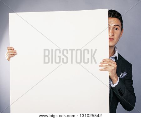 young handsom businessman in suit with poster empty copy space smiling, lifestyle advertising people concept