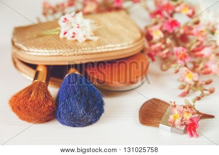 There White and Pink  Branches of Chestnut Tree,Bronze Powder;Two Make Up Brown and Blue Brushes in the Golden Cosmetic Bag are on White Table,Selective Focus,Toned