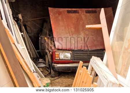 Old red car in old garage at day