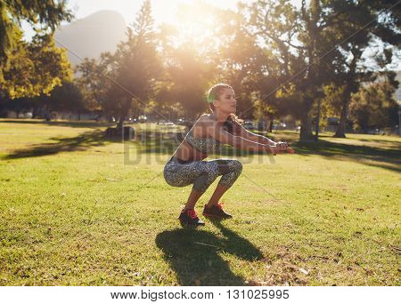 Fit Young Woman Doing Squatting In Park