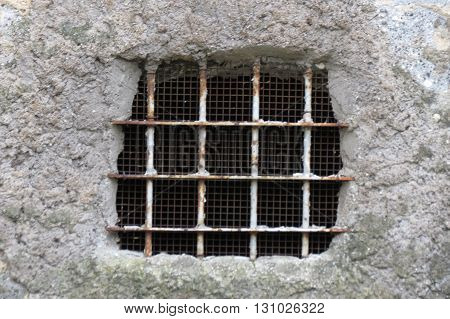 Old window opening in a stone wall with iron gratening