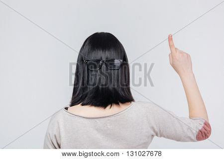 Back view portrait of a brunete girl pointing finger up isolated on a white background