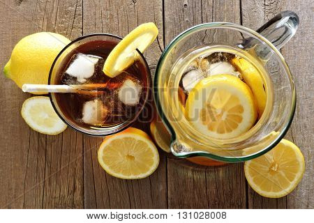 Pitcher And Glass Of Iced Tea With Lemon Slices, Downward View On A Rustic Wood Background