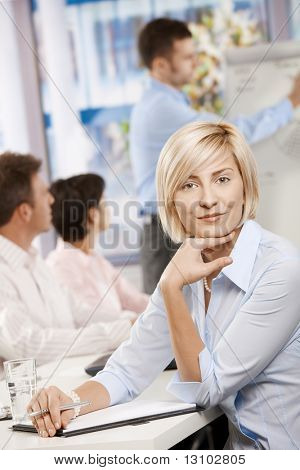 Young businesswoman sitting on business meeting in office making notes, looking at camera smiling.