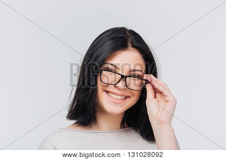 Beautiful smiling brunette touching glasses on white background
