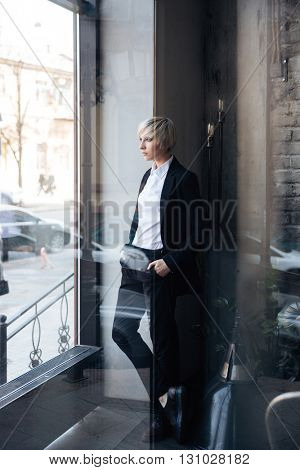 Beautiful young girl standing near the window in cafe, looking at the window, street reflection in window