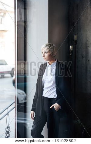 Stylish young girl standing near the window? street reflection in window
