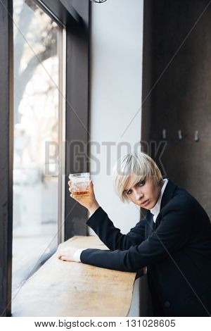 Beautiful blonde girl standing at the windowsill and holding glass in cafe