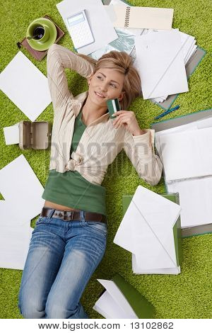 Happy woman lying on floor holding credit card, bills all around.