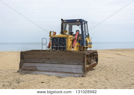 Yellow old tractor on a sandy sea beach.