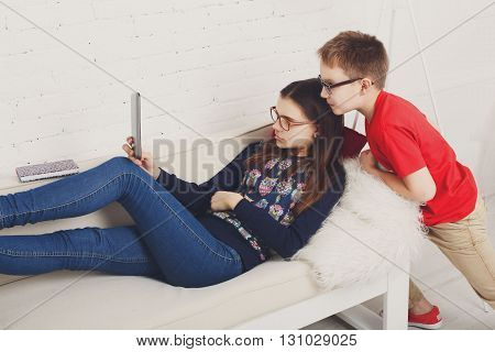 Group of kids in eye glasses look into tablet. Children computer games, social networks and media addiction concept. Girl and boy with tablet. Communication technologies. Eyesight, eyewear for kids.