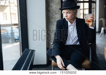 Beautiful stylish girl sitting in the chair and drinking in cafe