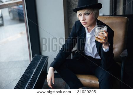 Stylish blonde girl in hat holding glass of whiskey and sitting in chair in bar looking at the window