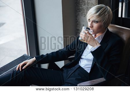 Beautiful stylish girl drinking and relaxing in chair in modern cafe