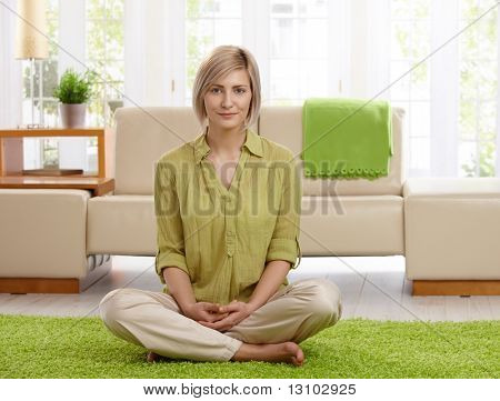 Smiling woman sitting with legs crossed on living room floor, looking at camera.