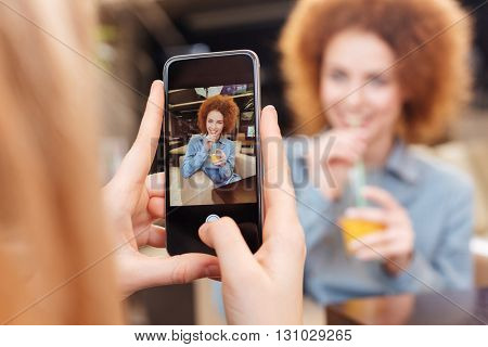 Woman using mobile phone and taking photos of her smiling curly young girlfriend drinking juice in cafe