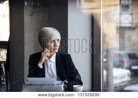 Pretty blonde girl thinking about something in modern cafe